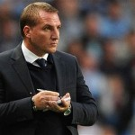 Brendan Rodgers stood pitch side with a pad and pen