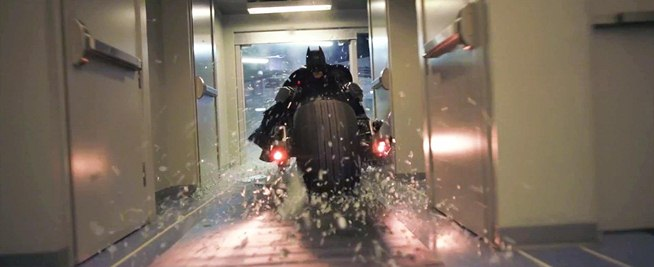 Batman on his motorbike smashing through a window, movie from the Dark Knight