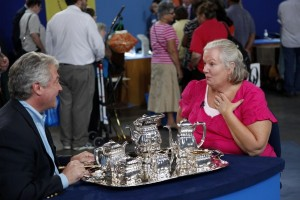 A photo of a lady and gentlement on the Antiques Roadshow TV programme with a silver tea set.